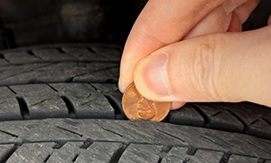 man using penny to check for tire tread